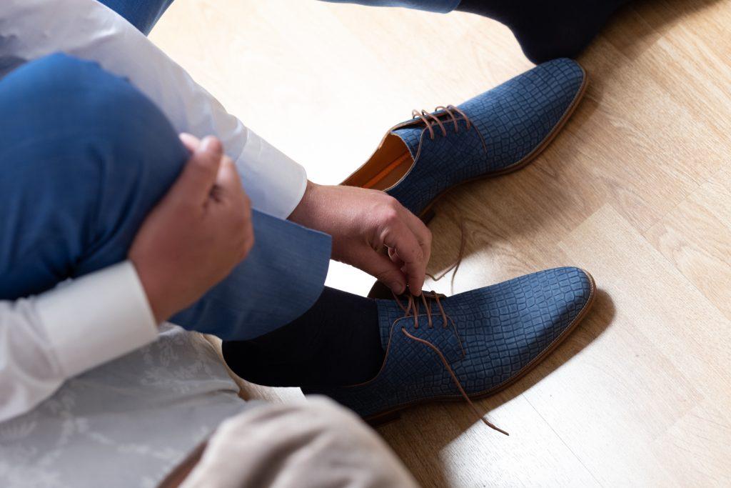 bruidegom trekt schoenen aan, bruiloft Arjan en Marion, Smilde © 2018 Matthijs Jonker Fotografie